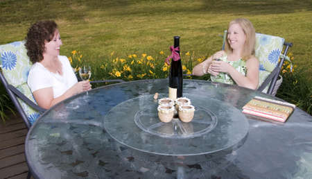 Two women sharing a laugh over wine on a patio