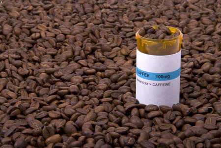 addiction drinking: A medicine bottle filled with coffee beans and surrounded by coffee beans. Stock Photo