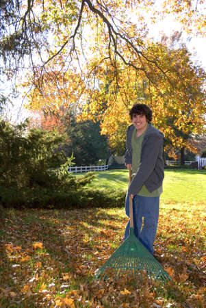 A teen boy with a rake and a yard full of leaves. photo