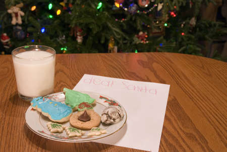Cookies and milk and a note for Santa by the Christmas tree. photo