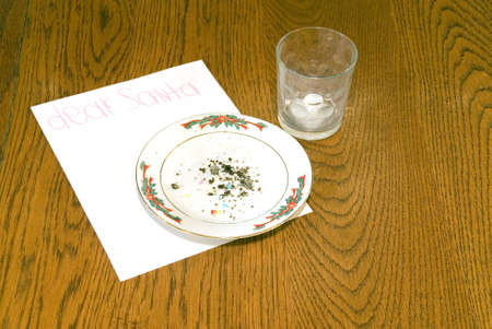 Cookie crumbs and an empty milk glass and a note for Santa. photo