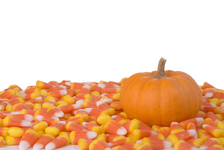 A little pumpkin surrounded by candy corn. Stock Photo
