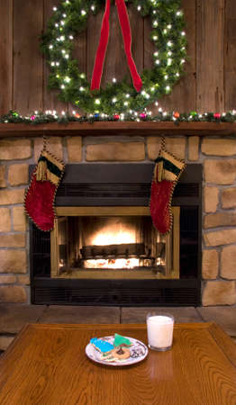 stone fireplace: Christmas cookies and milk on a table by a fireplace waiting for Santa Claus.