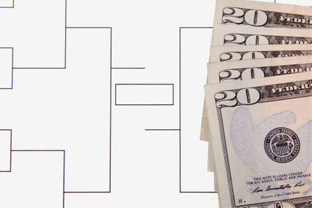 A closeup of a final four bracket and twenty dollar bills. photo