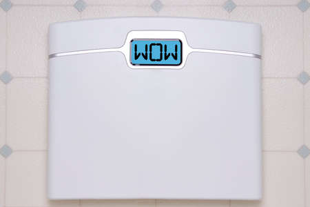 A white digital bathroom scale displaying the text message WOW.