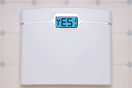 A white digital bathroom scale displaying the text message YES.