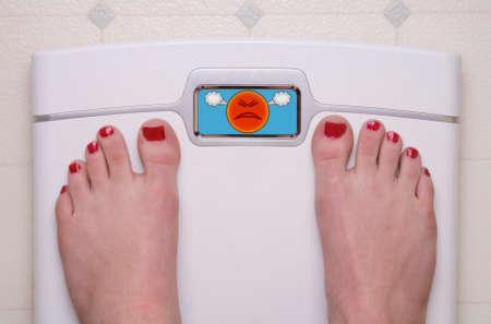 Digital Bathroom Scale Displaying an Angry Emoji Stock Photo