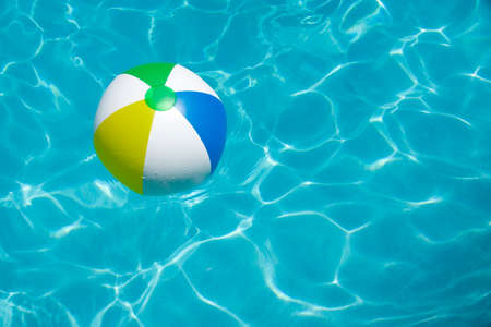 pool balls: A colorful beach ball floating in a swimming pool  Stock Photo