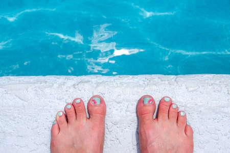 u�as pintadas: U�as de los pies pintadas en el borde de una piscina Foto de archivo