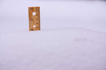 A ruler stuck in 10 inch deep snow. photo