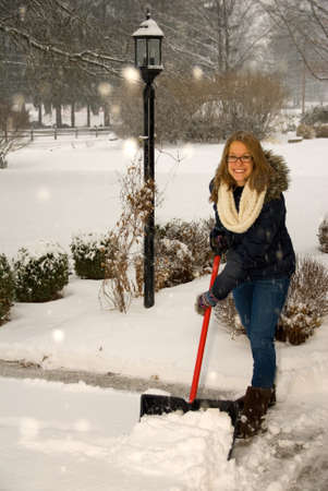 A young woman starting to shovel snow off the driveway.
