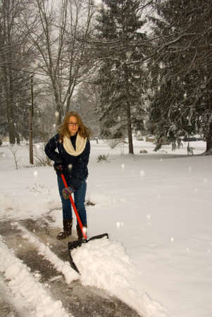 shoveling: A young woman shoveling snow off the driveway like a plow. Stock Photo