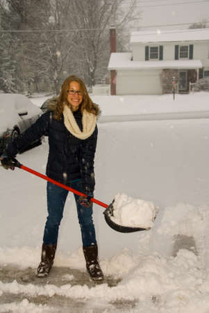 shoveling: A young woman happy to be shoveling snow in a blizzard. Stock Photo