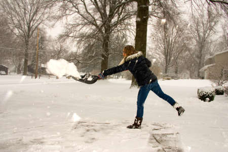 shoveling: A young woman throwing snow while shoveling.