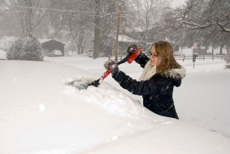 A young woman scraping snow off a car windshield.