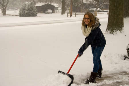 A young woman happy to be shoveling snow.