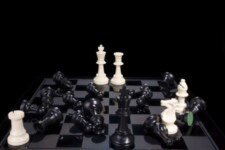 A chess board showing white pieces in checkmate and black pieces scattered.