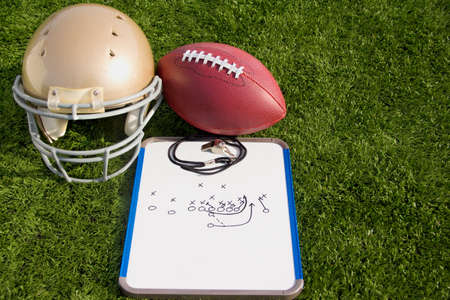 super bowl: A gold helmet, football and clipboard on a field.