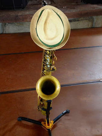 A straw hat itting on a saxophone on stage