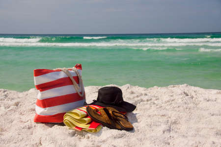 A beach bag, floppy hat, towel and Sandals at the beach.