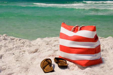 Una borsa da spiaggia e sandali sulla sabbia vicino al mare
