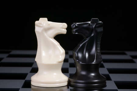White and black chess knights in conflict