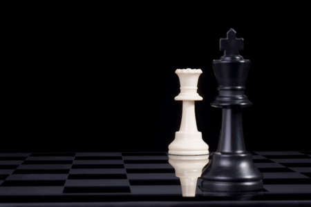 A black chess king in checkmate by white queen. Stock Photo