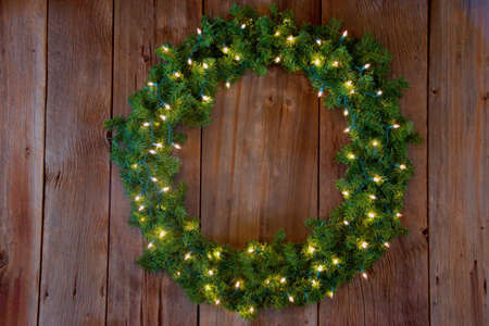 A green wreath with twinkle lights on a cedar background