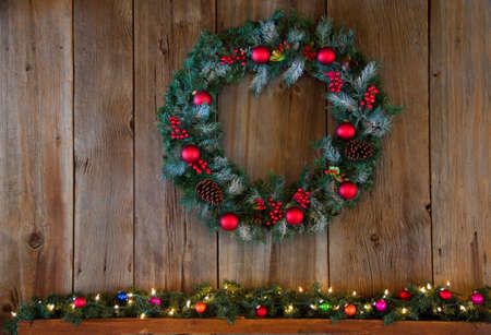 A winter wreat hanging over a mantle decorated for Christmas. Banque d'images