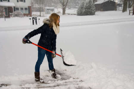A young woman ready to throw a shovel full of snow