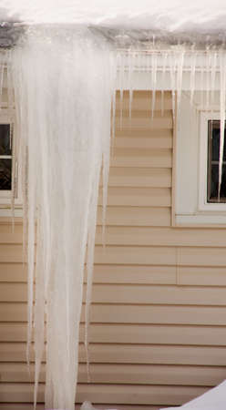 A giant icicle and ice dam on the roof of a house