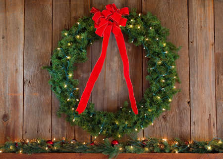 A Christmas wreath hanging on a cedar wall with a red ribbon