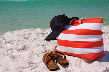 A beach bag, hat and sandals lying on the beach.