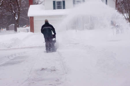 A man uses a snowblower on his driveway during a blizzard