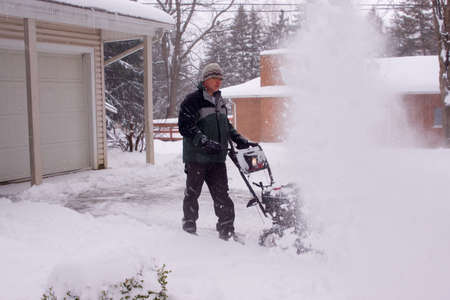 A man using a snowblower during a blizzard. Stock Photo