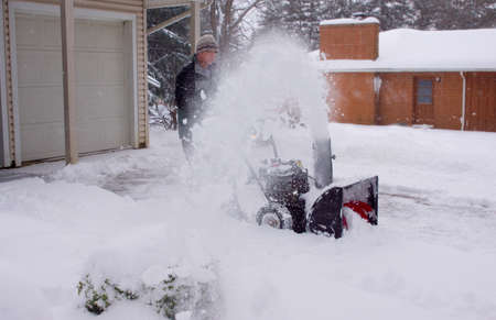 a man using a snowblower during a blizzard Imagens