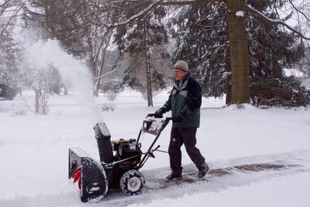 A man using a snowblower during a blizzard