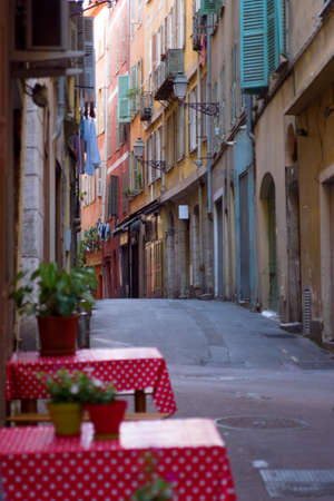 A deserted European street with dining tables in foreground