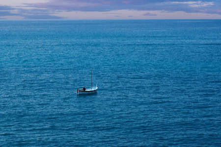 A lone fishermanin a small boat in the ocean Imagens
