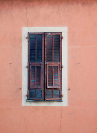 Old wooden window shutters on a pink stucco building Imagens
