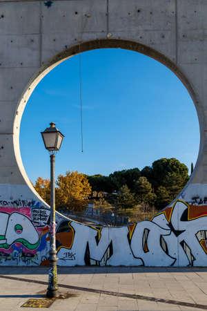 vetical: vista de un poste de luz y una ventana circular en una escultura urbana en Madrid, en la pared de fondo de una escultura tallada t�pica, Espa�a