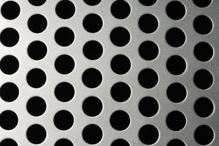 computing machine: Close-up of speaker grill with abstract pattern of circles.