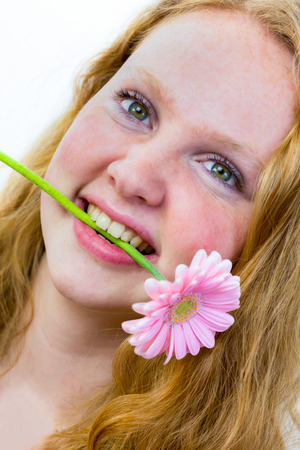 dutch girl: Face of dutch teenage girl with pink flower in her mouth