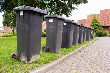 Grey garbage containers in a row standing along street