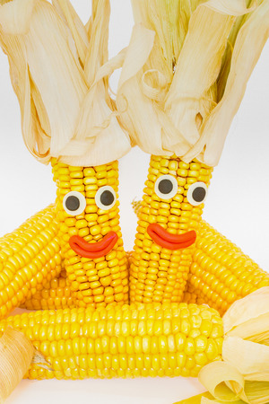 mais: Corncobs with eyes and mouth isolated on white background Stock Photo