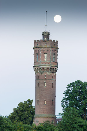 ethos: Brick watertower as building with full moon and trees