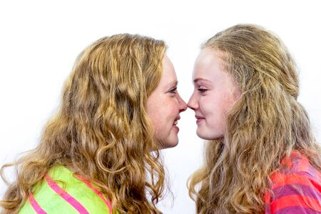 touching noses: Two european teenage sisters noses touching isolated on white background