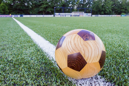 wood turning: Wooden football lying on sideline with goal in background