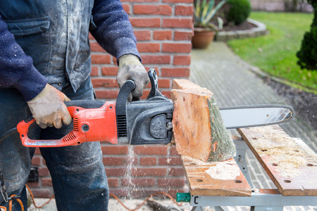 work clothes: Man in work clothes holding chain saw cutting wood of trunk on table outdoors