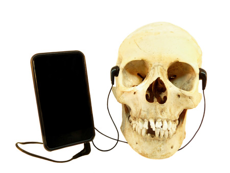 listening device: Human skull listening music on mobile device with earphones isolated on white background